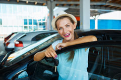 Happy woman standing near a car with keys in hand - concept of b Royalty Free Stock Image