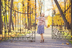 Happy woman standing near the entry gates to the park in autumn Royalty Free Stock Image