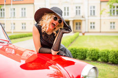 Happy woman standing next to vintage car Royalty Free Stock Photo
