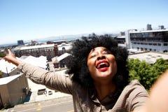Happy woman standing outside in city taking selfie Stock Photo