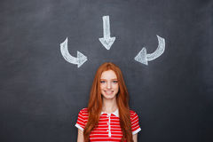 Happy woman standing over blackboard background with drawn arrows Royalty Free Stock Photo