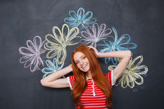 Happy woman standing over chalkboard with drawn colorful flowers Royalty Free Stock Photo