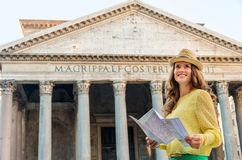 Happy woman standing by the Pantheon holding map in Rome Royalty Free Stock Photo