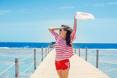 Happy woman standing on pier with big white hat Stock Photography