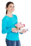 Happy woman standing with piggybank and notebooks Royalty Free Stock Image
