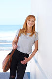 Happy woman standing with purse with sea in background Stock Images