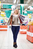 Happy woman standing with shopping bags on store Royalty Free Stock Photography