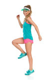 Happy Woman Standing Tiptoe On One Leg. Happy beautiful young woman in pink shorts, green tank top, sneakers and green sun visor standing tiptoe on one leg and Stock Images