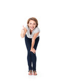 Happy woman stands at studio and showing thumbs up gesture Royalty Free Stock Photography