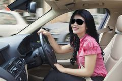 Happy woman steers a car Stock Images