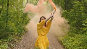 Happy woman stepping in color smoke through forest stock video
