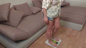 Happy woman stepping on weighing scale stock video footage