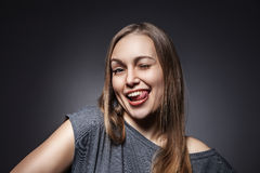 Happy Woman Sticking Out Her Tongue Over Grey Stock Image