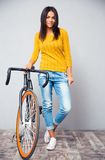 Happy woman stnading with bicycle Royalty Free Stock Images