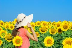 Happy woman with straw hat in sunflower field.  Stock Images