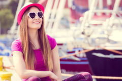 Happy woman with straw hat and sunglasses in port with yacht in background, summer time Royalty Free Stock Image