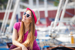 Happy woman with straw hat and sunglasses in port with yacht in background, summer time Royalty Free Stock Photo