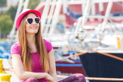 Happy woman with straw hat and sunglasses in port with yacht in background, summer time Stock Photo