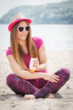 Happy woman in straw hat and sunglasses using sun lotion, sun protection on beach Royalty Free Stock Photography
