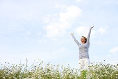 Happy woman with stretched arms in flower field Stock Photo