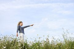 Happy woman with stretched arms in flower field Royalty Free Stock Images