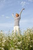 Happy woman with stretched arms in flower field Royalty Free Stock Photo