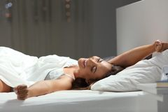 Happy woman stretching arms on a bed in the night Royalty Free Stock Photo