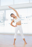 Happy woman stretching hand in fitness studio Royalty Free Stock Image