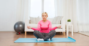 Happy woman stretching leg on mat at home Stock Image