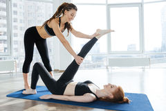 Happy woman stretching legs with personal trainer Stock Photography
