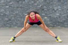 Happy woman stretching before starting her workout royalty free stock photography