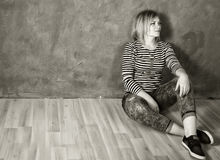 Happy woman in a striped t-shirt and jeans sitting on wooden floor Stock Image