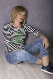 Happy woman in a striped t-shirt and jeans sitting on wooden floor Royalty Free Stock Image