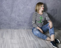 Happy woman in a striped t-shirt and jeans sitting on wooden floor Royalty Free Stock Images