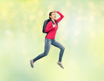 Happy woman or student with backpack jumping Stock Photo