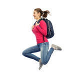 Happy woman or student with backpack jumping. Education, travel, tourism, motion and people concept - smiling young woman or student with backpack jumping in air Stock Image