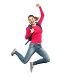 Happy woman or student with backpack jumping. Education, travel, tourism, motion and people concept - smiling young woman or student with backpack jumping in air Royalty Free Stock Image