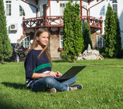 Happy woman student sitting on grass with laptop. Beautiful casual female outdoor using pc. Royalty Free Stock Photo