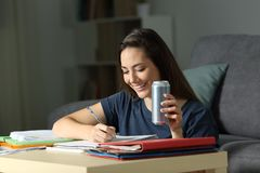 Happy woman studying holding energy drink. Happy woman studying late hours holding energy drink at home in the night Royalty Free Stock Images
