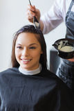 Happy woman with stylist coloring hair at salon Stock Image