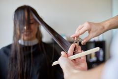 Happy woman with stylist cutting hair at salon. Beauty, hairstyle and people concept - happy young women and hairdresser hands with scissors and comb cutting Royalty Free Stock Photos
