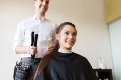Happy woman with stylist making hairdo at salon Royalty Free Stock Image