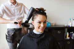 Happy woman with stylist making hairdo at salon Stock Photography