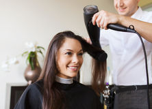 Happy woman with stylist making hairdo at salon Royalty Free Stock Photos