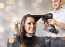 Happy woman with stylist making hairdo at salon Stock Photo