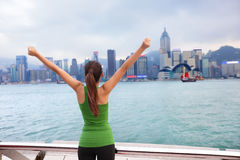 Happy woman success cheering by Hong Kong skyline. With arms raised up outstretched. Successful winner celebrating cheerful on Tsim Sha Tsui Promenade and Royalty Free Stock Images