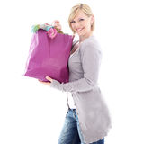 Happy woman after a successful shopping spree. Happy woman smiling in glee after a successful shopping spree as she carries home a carrier bag crammed full of Royalty Free Stock Photography