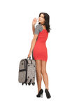 Happy woman with suitcase waving hand Royalty Free Stock Photos