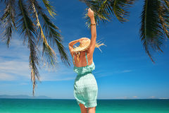 Happy woman in summer dress jumping against blue sky and ocean. Royalty Free Stock Photography