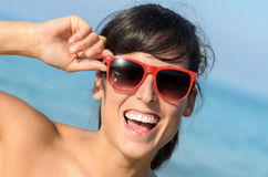 Happy woman summer fun on beach. Happy woman face on summer vacation. Brunette girl having fun on beach wearing sunglasses Royalty Free Stock Images